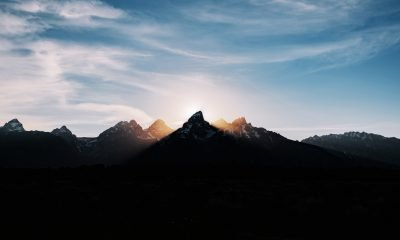 Silhouette of mountain with sun behind it's peak